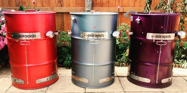 three different color drum smokers
